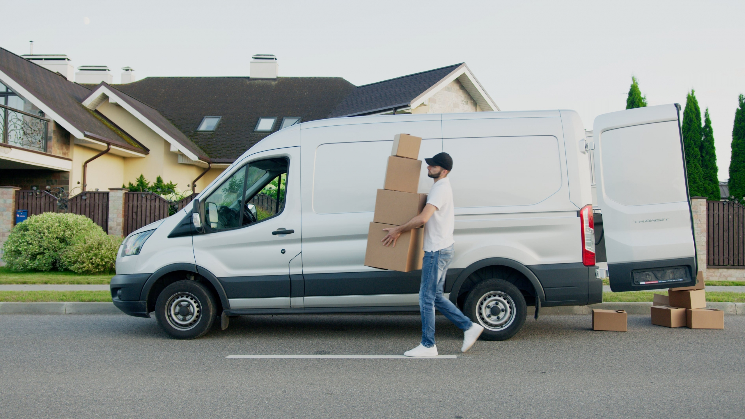 Fahrer liefert Pakete vor einem Van aus